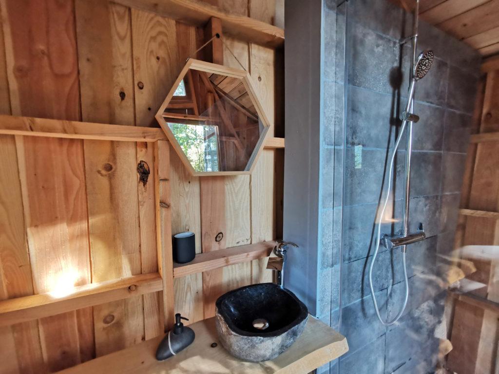 Salle de bain bulle transparente Olea avec douche et lavabo dans cabane en bois